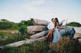Adventure engagement session at sunset in a field with the couple sitting on a pile of old wooden logs