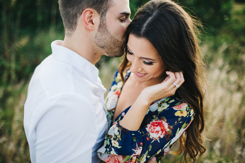 Bride wearing cute floral romper for Florida engagement session at sunset