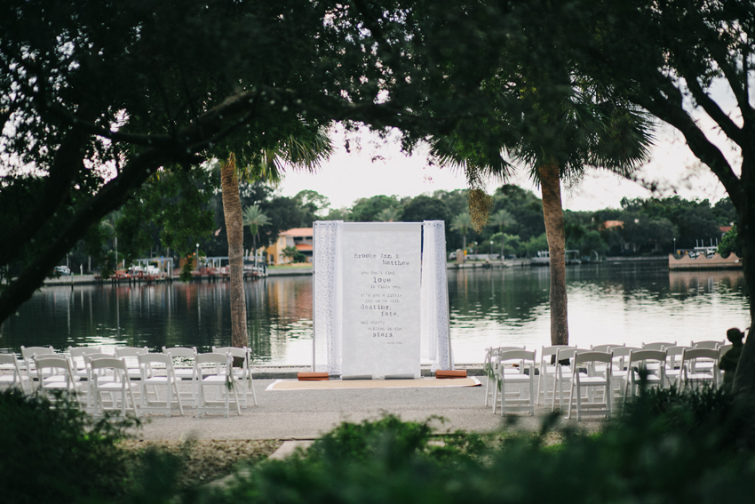 outdoor waterfront wedding ceremony with diy quote fabric backdrop