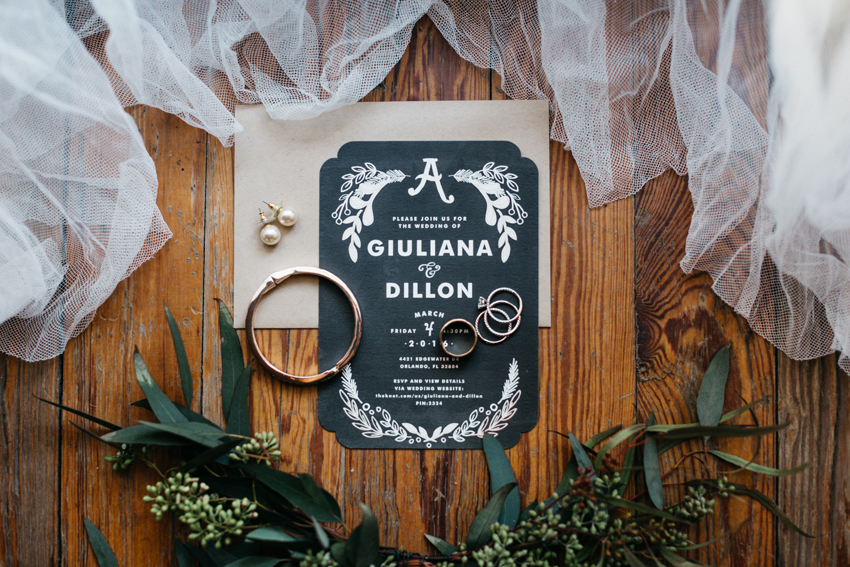 chalkboard wedding stationery surrounded by greenery on a wooden floor