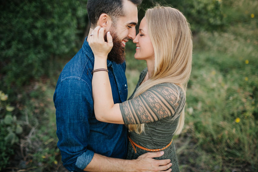 Cute couple standing in a field of wispy grass for engagement photos and anniversary photos