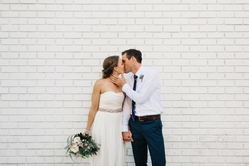 St. Pete Wedding Photographer with natural light, candid wedding photos against a brewery white brick wall