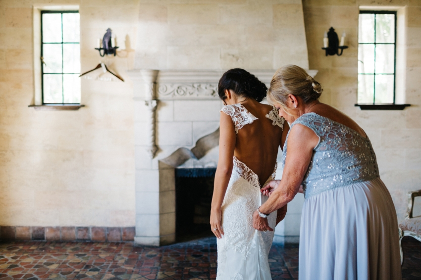 bride putting on her lace dress with a zip up button back