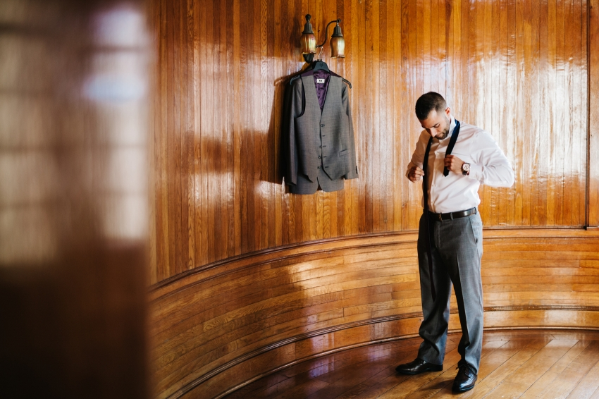 Groom putting on his custom grey suit before the wedding