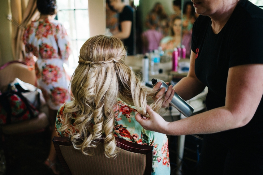 Bridesmaid getting her hair done with a half updo french braid