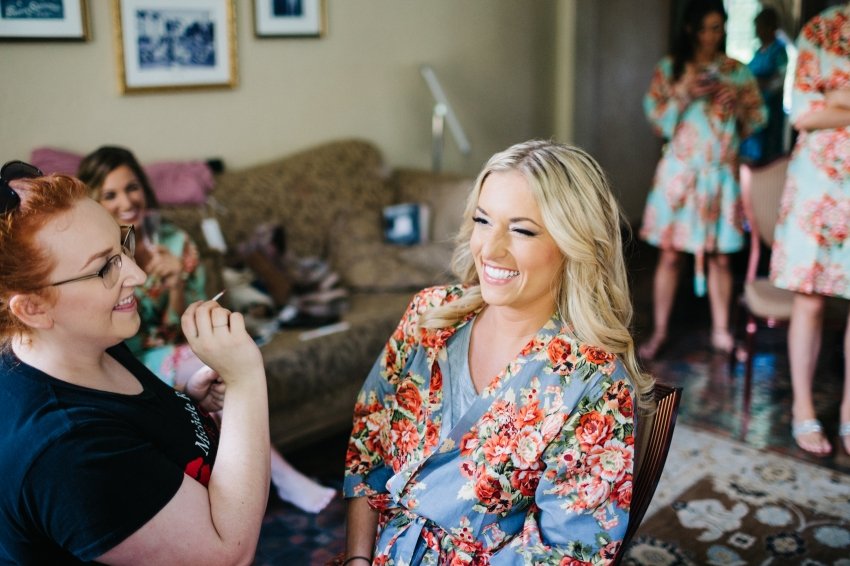 bridesmaid wearing a silk floral robe while she gets her makeup done before the wedding