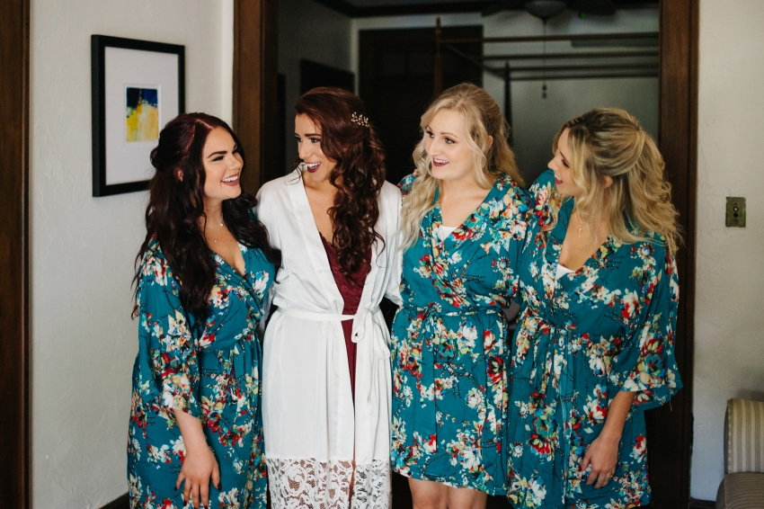 bride and bridesmaids wearing lace floral robes while the get ready for the ceremony