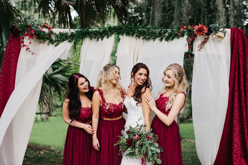 Bridesmaids wearing crop top maroon burgundy dresses