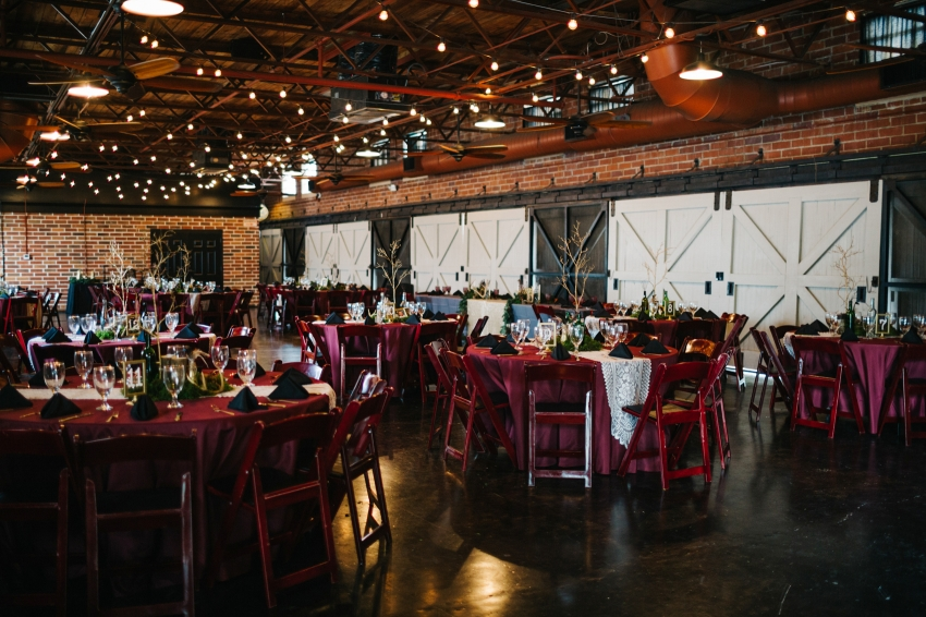 Burgundy boho wedding reception at the Winter Park Farmers Market with exposed brick walls and string lights
