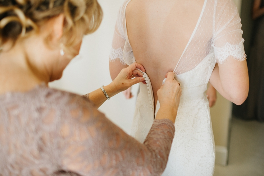 mother of the bride wearing a lavendar lace dress helping the bride get ready
