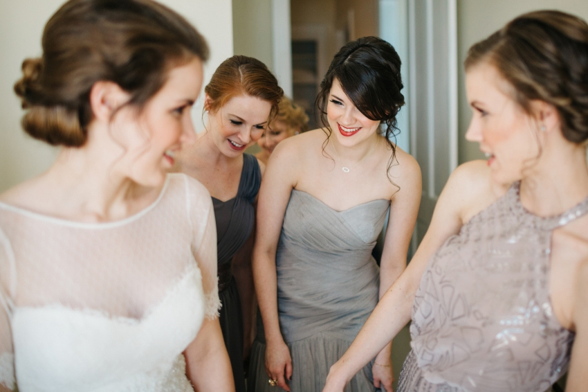 bridesmaids wearing mismatch grey dresses helping the bride get ready