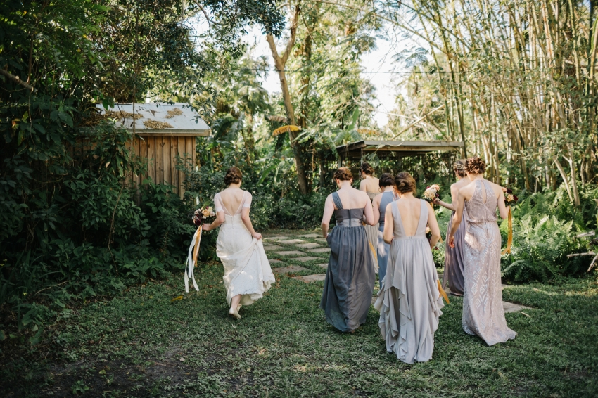 Bride and her bridesmaids wearing mismatched grey dresses walking through the garden