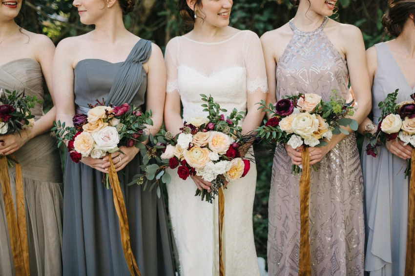 lush romantic wedding bouquets with burgundy, blush, and gold tied with mustard and ivory loose ribbon