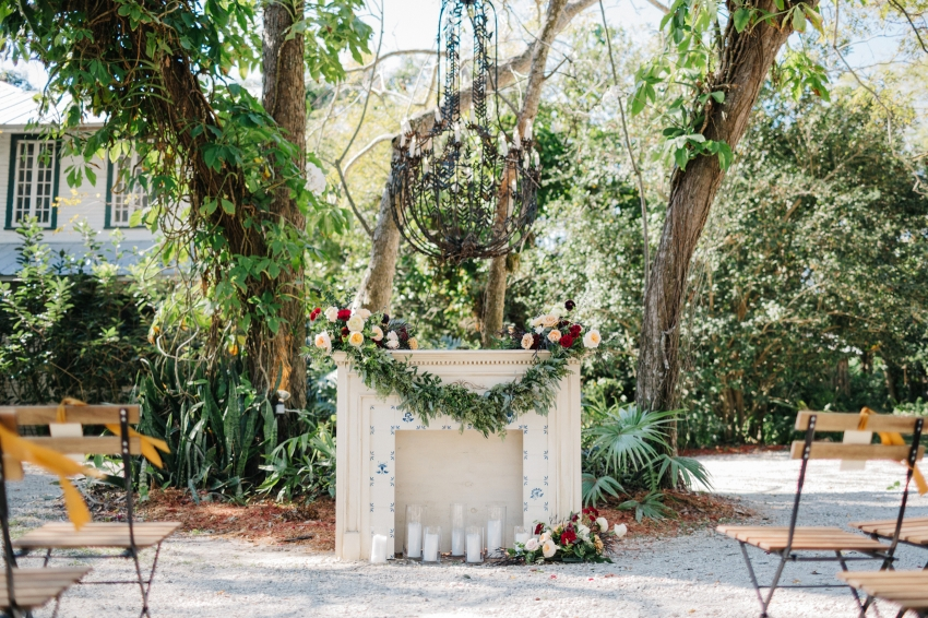 vintage mantle at the garden ceremony with romantic candles and a garland of greenery and flowers
