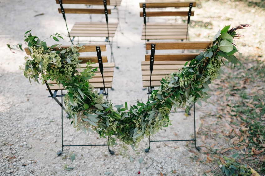 a garland of greenery around the ceremony chairs