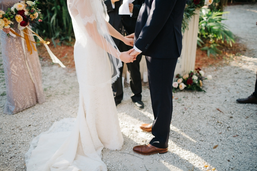 Bride and groom holding hands during the cermeony