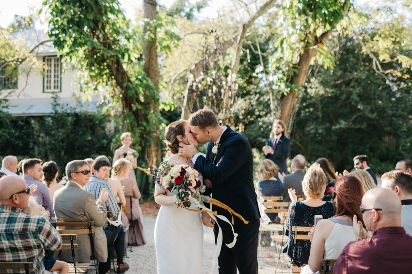Bride and groom sharing their first kiss at the eclectic romantic secret garden ceremony