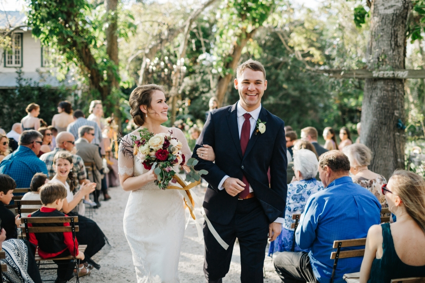 bride and groom laughing and smiling as they walk down the aisle after exchanging vows at their Orlando garden wedding outdoor ceremony