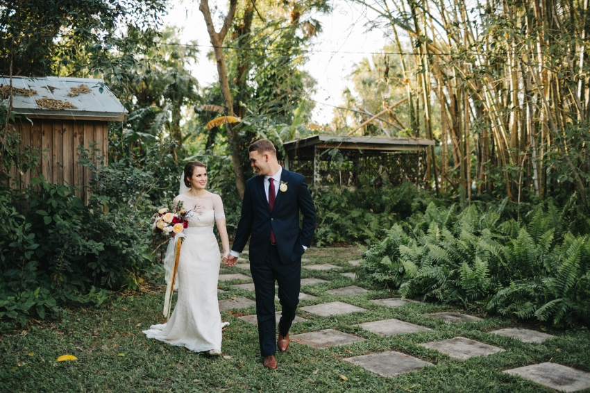 Candid wedding portrait of the bride and groom walking in the garden after their Florida outdoor ceremony