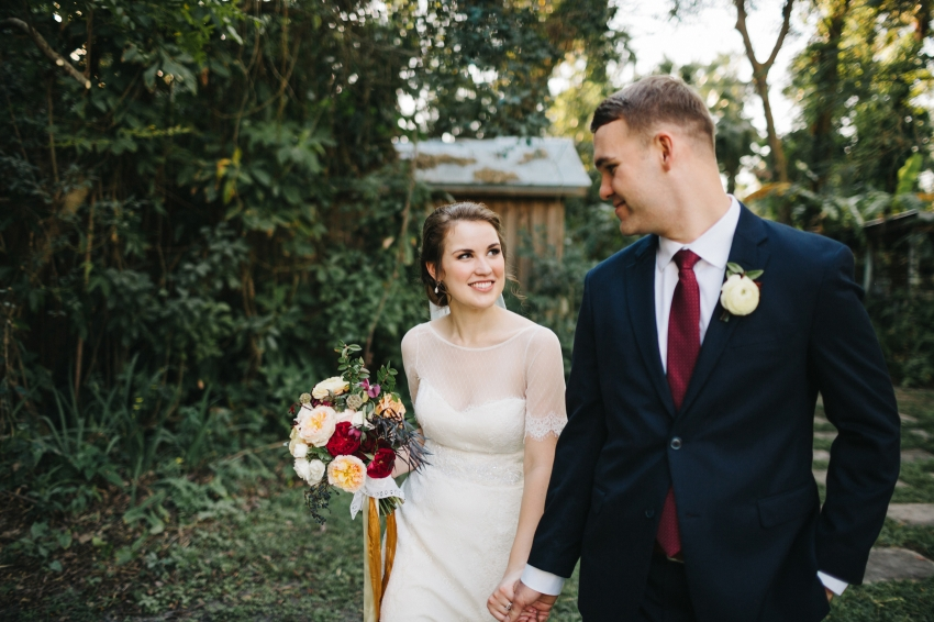 bride smiling at her groom carrying a lush burgundy, peach, and gold wedding bouquet