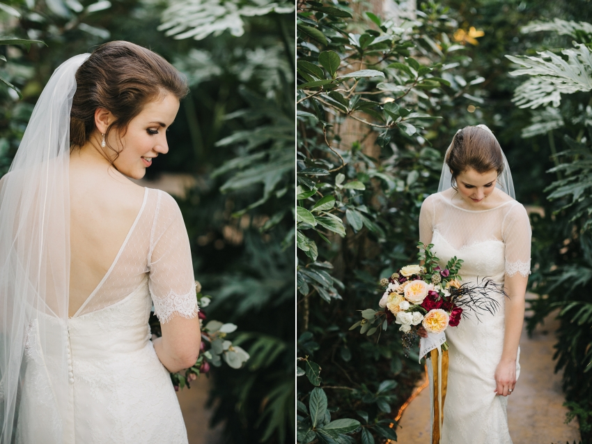 Bride wearing a gorgeous sleeved wedding dress and holding a lush boquuet of burgundy, peach, and gold peonies and garden roses