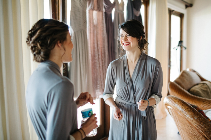 bridesmaids laughing while they get ready for the wedding wearing light grey robes with lace trim sleeves