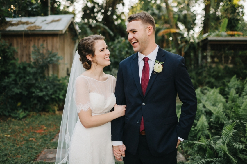 groom wearing a burgundy tie and laughing with his bride in the garden at their outdoor ceremony in the garden near Orlando, Florida by Florida wedding photographer