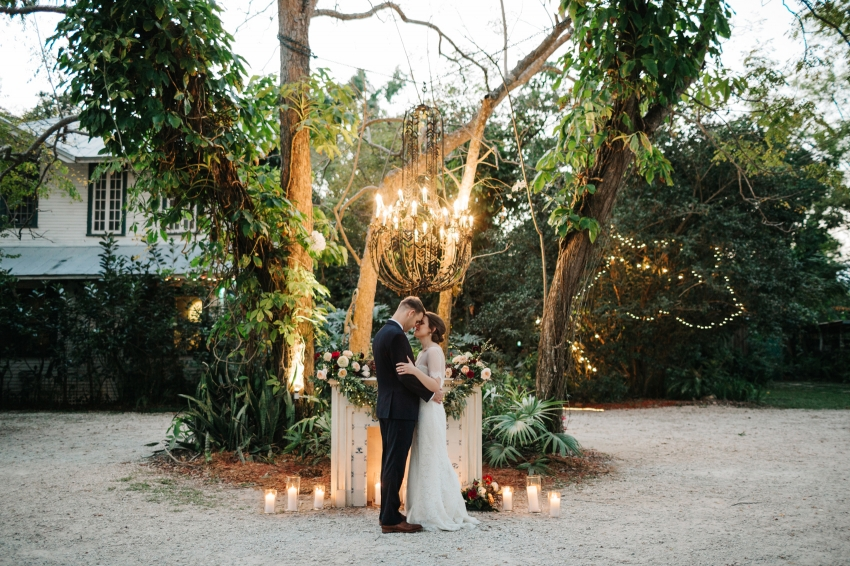 Romantic Orlando wedding photos at dusk with candles and stringlights in front of a vintage fireplace in the garden wedding