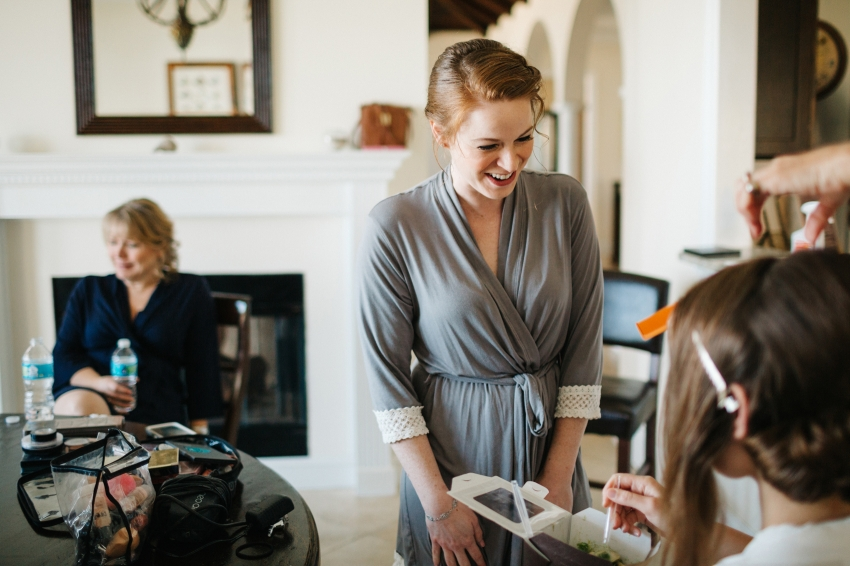 bridesmaid laughing with the bride in her light grey robe