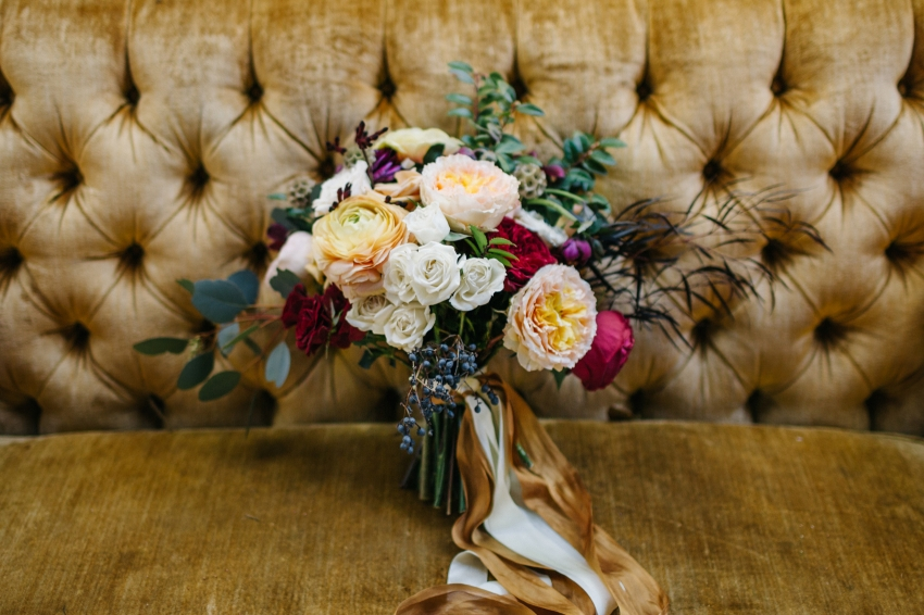 Lush bouquet of burgundy, peahc, and gold peonies and garden roses sitting on a vintage mustard couch for outdoor Orlando garden wedding