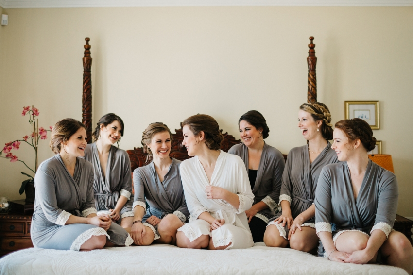 bride and her bridesmaids wearing their robes and sitting on the bed laughing