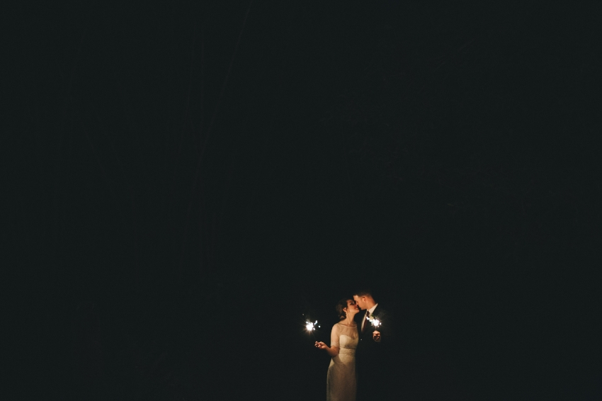 romantic wedding sparkler photo with the bride and groom