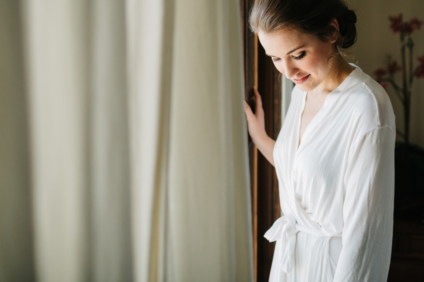 bridesmaid wearing a white lace bridal robe while she gets ready to put her Amy Kuschel 'London' dress on