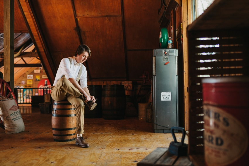 groom wearing suspenders and khaki pants putting on his shoes inside the rustic barn