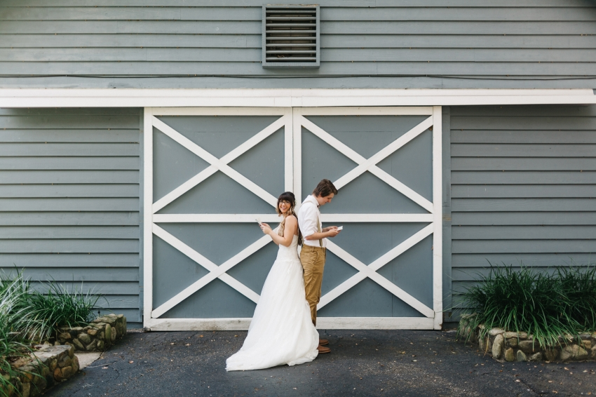 bride and groom sharing a sweet first look by exchanging letters infront of the dusty blue barn at the Lange Farm in Florida