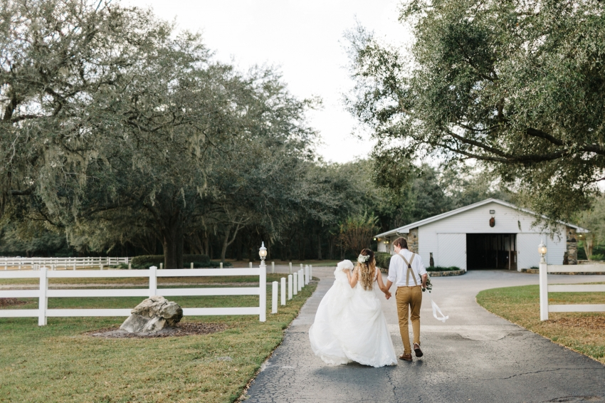 bride and groom walking through the rustic farm by the white barn in Florida before their wedding