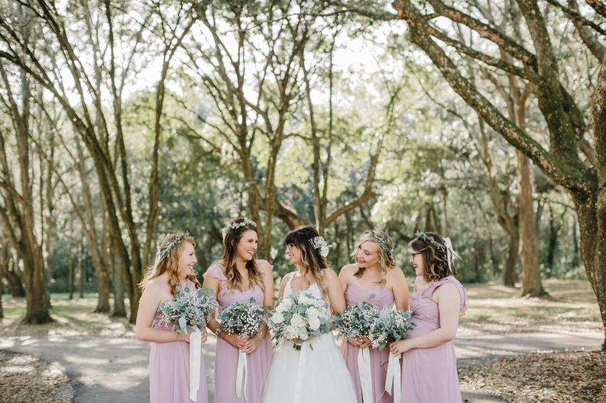 bridesmaids wearing dusty pink gowns laughing with the bride under the oak trees at the Lange Farm barn venue