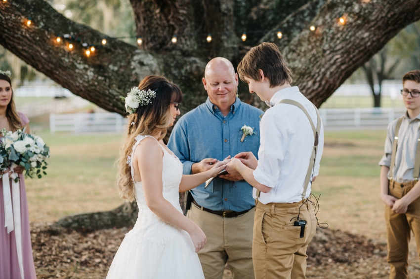groom slipping on the wedding band during the outdoor ceremony under the oak trees in tampa, florida