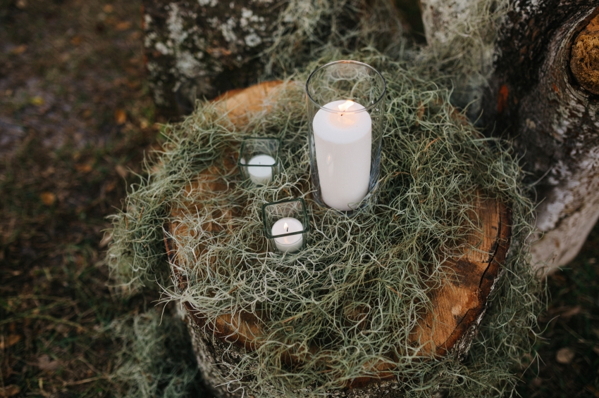 rustic ceremony decor with tree stumps and moss