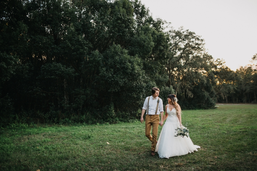 bride and groom walking along the rustic farm before their barn reception under the twinkle lights in tampa, florida