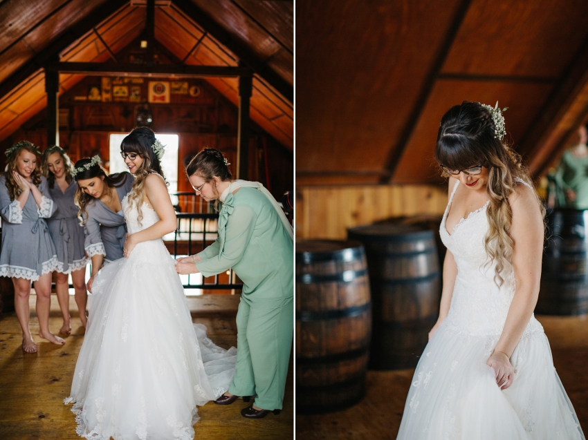 bride putting on her dress at the rustic barn on the Lange Farm Property