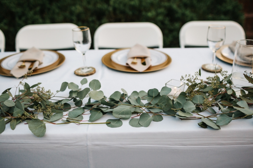 greenery table runners for rustic barn wedding with gold chargers and tree slice coasters