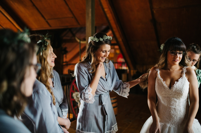 bridesmaids wearing floral crowns and grey robes while getting ready for rustic wedding